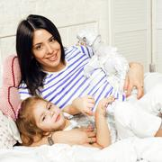 Portrait of smiling young mother and daughter at home, happy family together Stock Photos