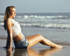 Young pretty blond woman at seacoast walking relaxing, fashion lady at sunset Stock Photos