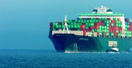 Cargo container ship and pusher tugs enter the sea port during the heat wave, 4K Stock Footage
