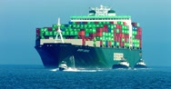 Cargo container ship and pusher tugs enter the sea port during the heat wave 4K Stock Footage