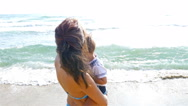 Mother hugging and kissing her little son at the sea beach Stock Footage