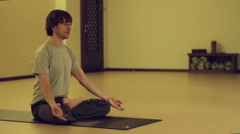 Man doing yoga asanas in the hall, then gets up, turns off the mat and goes Stock Footage