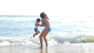 Mother and little son playing with sea waves Stock Footage