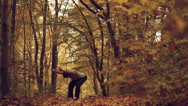 Man doing yoga asanas in the autumn forest Stock Footage