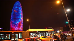 Creative light show on Torre Agbar skyscraper, active traffic in night Barcelona Stock Footage