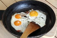 Fried eggs with bacon on the pan -  hearty breakfast Kuvituskuvat
