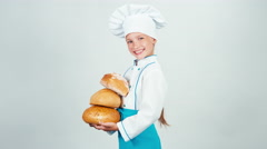 Young baker holds three loaves of bread in her hands and smiling at camera Stock Footage