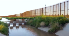 A Muddy River and Large Fence Separates Two Countries Stock Footage