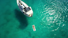 Aerial view of a woman relaxing on raft next to sailboat in the Caribbean Stock Footage