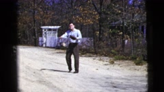 1956: man smoking a cigarette plays catch and uses a baseball mitt in the street Stock Footage