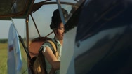 Happy woman pilot in old airplane at sunset Stock Footage
