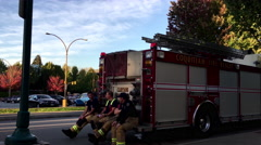 Coquitlam fire emergency personnel resting and chatting on fire truck Stock Footage