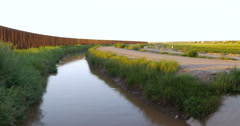 A River and a Large Metal Fence Stretch into the Horizon Stock Footage