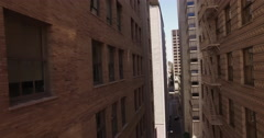 Drone flying backwards in a tight alley with tall apartments Stock Footage