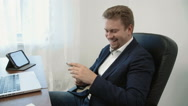 Young businessman working in his office in front of the laptop computer. He uses Stock Footage