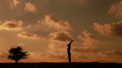 Man doing yoga asanas on a background of clouds and near the small tree Stock Footage