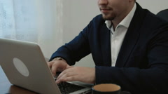 Young businessman working in his office in front of the laptop computer gets a Stock Footage