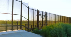 Panning Along the Fence and River Dividing Countries Stock Footage