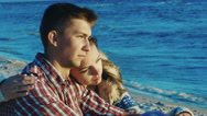 Romantic couple relaxing on the beach, she clung to the guy. Sunny and windy day Stock Footage
