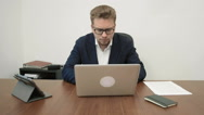 Young stressed out businessman working intensively in his office in front of the Stock Footage