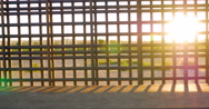 Sunlight Flickers Between the Bars of the Border Fence Dividing Countries Stock Footage