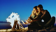 Young couple sitting by the fire in the evening, warm your hands by the fire Stock Footage