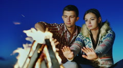 A loving young couple sitting on the beach campfire. Warm hands by the fire Arkistovideo