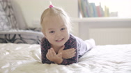 Smiling little girl lying on the bed Stock Footage