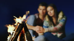 Romantic couple talking softly in the burning fire. Sharpness on the fire, a Stock Footage