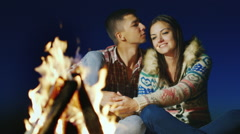A loving couple sitting by the fire, holding hands, admiring fire Stock Footage