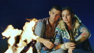 Young couple relaxing by the fire, drinking a beer or a drink from the bottle Stock Footage
