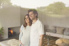 Smiling pregnant couple looking out living room window Stock Photos