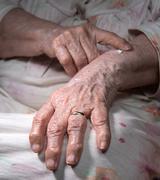 Old woman applying hand cream Stock Photos