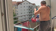 The man on the balcony shoots washed things dried out Stock Footage