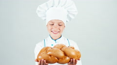 Portrait young baker holds braided bread and gives loaf you at camera smiling Stock Footage