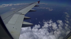 Plane flying above the sea and puffy clouds Stock Footage