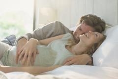 Affectionate pregnant couple laying in bed laughing Stock Photos