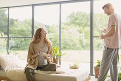 Pregnant couple eating cereal and drinking coffee in living room Stock Photos