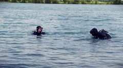 Divers descend in the lake with OK sign Stock Footage