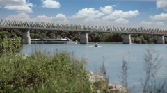 Two trains crossing the bridge at the same time, tourist ship on the river Stock Footage