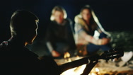 The company of friends relaxing by the fire, a man plays guitar Stock Footage