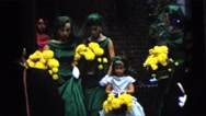 1962: bridesmaids in green and pink dresses and white gloves carrying bouquets Stock Footage