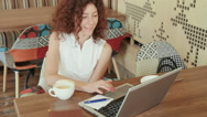 Woman in a cafe , drinking coffee and working on the laptop Stock Footage