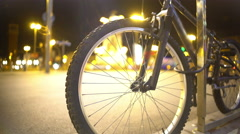 Defocused night city lights and pedestrians seen through bicycle wheel spokes Stock Footage