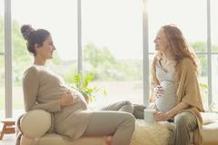 Pregnant women drinking tea and talking in living room Stock Photos