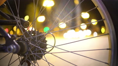 Active night city timelapse seen through bicycle wheel, hectic urban lifestyle Stock Footage