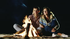Two video : Man and woman relaxing evening around the campfire, roast Arkistovideo