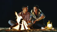 Man and woman relaxing evening around the campfire, roast marshmallows on sticks Stock Footage