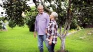 Senior couple walking along summer garden Stock Footage