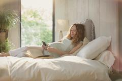 Pregnant woman laying relaxing with book and texting with cell phone in bed Stock Photos